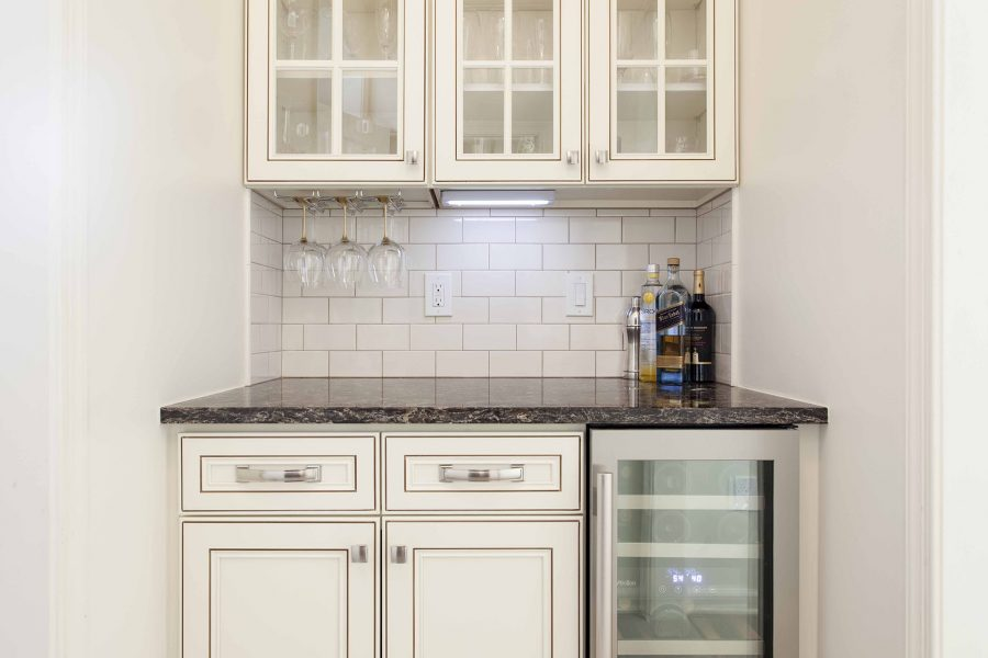 Bar section with wine cooler and wine glass hanger attached to the wall cabinet